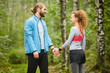 Young sportswoman touching hand of her mate or boyfriend during sports training in the forest