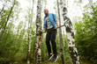 Young sportsman pulling up on gymnastics bar between two birches in the forest while exercising in the morning
