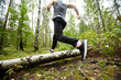 Young active man running through birch log on forest path during morning training