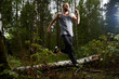 Active man in sportswear having morning run in birch forest and enjoying summer morning