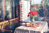 Rural life spring scene. April dinner near the house at sunset with tulips on the table - 243266295
