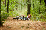Young sportswoman fell off her bicycle and hurt her leg on forest path during morning ride