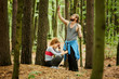 Young man with smartphone catching signal to call for help while sad woman with hit leg sitting by tree