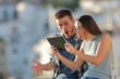 Leinwandbild Motiv Amazed friends finding online content on a tablet outdoors