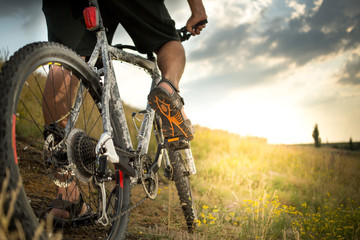 Mountain bike. Low angle view of cyclist riding mountain bike on rocky trail at sunset