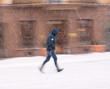 Woman walking down the street in winter snowy day in motion blur - 243278663