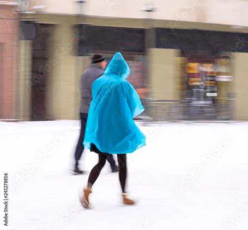 Woman walking down the street in winter snowy day in motion blur - 243278856