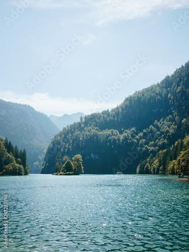 Leinwanddruck Bild Landscape with lake against mountains