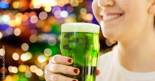 alcohol and st patricks day concept - close up of woman with green beer in glass over festive lights background