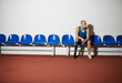 Young disable man with artificial leg sitting on chair along wall and waiting for his turn for game