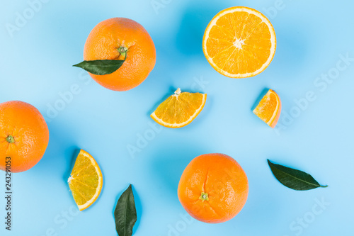 Slices of orange with leaves on blue background. Flat lay, top view.