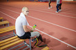 Young active man with handicapped right leg having break and refreshment on bench after training