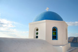 Traditional white church with a Blue dome, perched on the side of the cliff, Oia, Santorini, Greece.