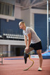 Young active man with handicapped leg doing exercise for knees before training on stadium
