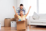 home, people, moving and real estate concept - happy couple having fun and riding in cardboard box at new home - 243293094