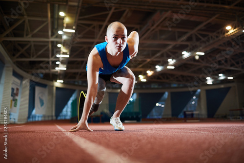 Poster Young active runner with handicapped leg standing by start line on race track and waiting for signal to go