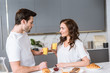Leinwanddruck Bild - attractive girlfriend looking at boyfriend while holding glass with orange juice in kitchen