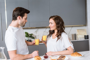 attractive girlfriend looking at boyfriend while holding glass with orange juice in kitchen