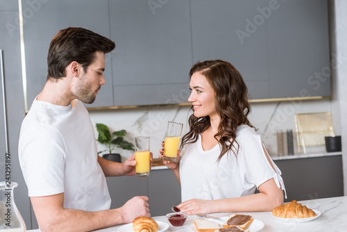 Leinwanddruck Bild attractive girlfriend looking at boyfriend while holding glass with orange juice in kitchen