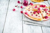 Idea for Valentine's Day surprise gift. Cute pancakes crepes with berry sauce and heart shaped cutouts. Romantic valentine breakfast. On wooden table, with fresh raspberries. Copy space - 243297875
