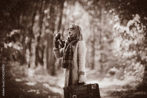Young girl with suitcase and camera in autumn season park.