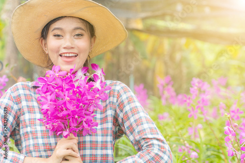 A woman gardener wearing a plaid shirt wearing a hat is holding a pink orchid in his hand. And was smiling happily. In the orchid garden - 243298639