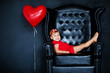 Little blonde girlin red dress with red wreath with hearts sitting on the armchair with red heart balloon on the St. Valentine's day. Black background