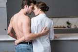 adult man and woman embracing at home with closed eyes - 243299269