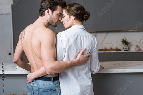 adult man and woman embracing at home with closed eyes