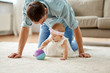 family, fatherhood and people concept - happy father and little baby daughter playing with ball at home - 243299460