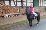 Junge beim Ausritt auf seinem Pony - 243300277