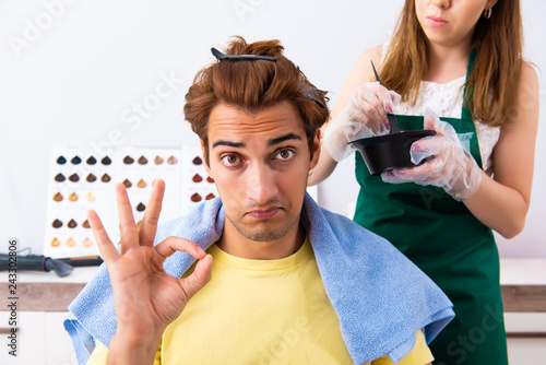 Woman hairdresser applying dye to man hair