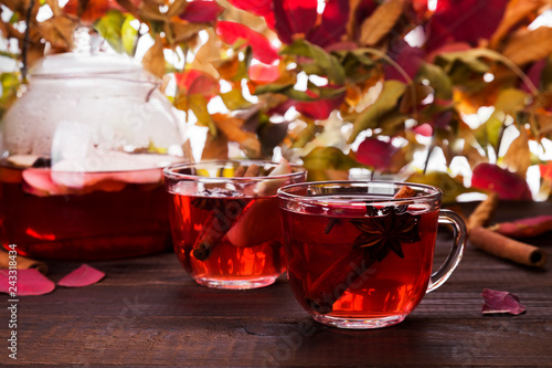 Hot drink with hibiscus red tea with apple, cinnamon and anise in glass teapot and two glasses on wooden background