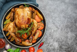 Roasted chicken, potatoes and vegetables in plate on grey background. Top view. With copy space - 243320092