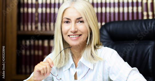 Portrait of a mature businesswoman smiling in her library © Minerva Studio