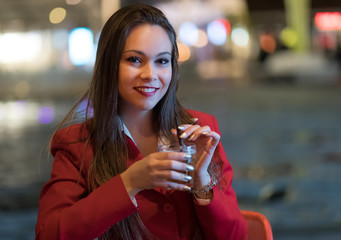 Young woman holding a drink at a night club outdoor © Minerva Studio