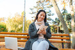 Smiling young asian woman wearing coat sitting on a bench - 243323242