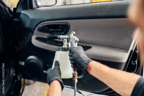 Carwash service, male worker in gloves using spray