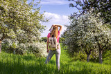 Woman tourist with backpack enjoying time in blooming orchard at spring - 243331280