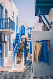 The narrow streets of the island with blue balconies, stairs and flowers. - 243333072