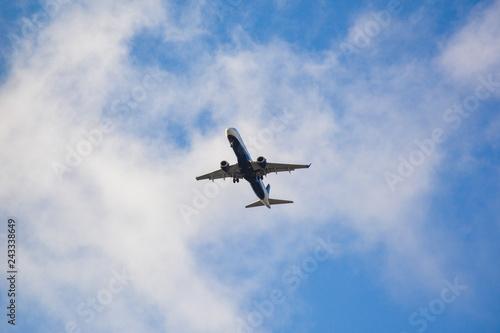 Passenger airplane landing against blue cloudy sky in Brazil