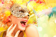 Leinwandbild Motiv Beautiful surprised woman in carnival mask. Beauty model woman wearing masquerade mask at party over holiday background with magic glow. Christmas and New Year celebration. Glamour lady with perfect