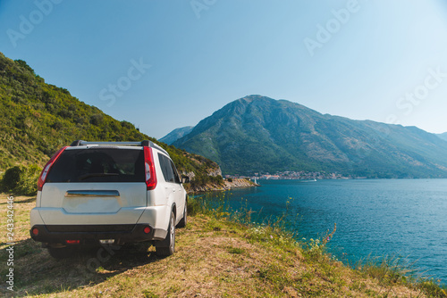 Fridge magnet white suv car parked at seaside with beautiful view of bay with mountains
