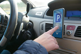 Driver using smartphone app to pay for parking - 243343473