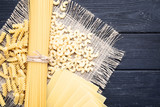 Different uncooked pasta with sackcloth on wooden table - 243343869