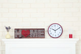 White fireplace with round clock, lavender and word Home - 243344289