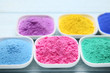 Colorful holi powder in bowls on wooden table