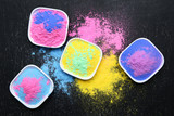 Colorful holi powder in bowls on black wooden table - 243344820