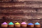 Colorful holi powder in bowls on brown wooden table - 243344840