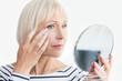 Beautiful elderly woman holding mirror and applying face cream